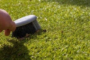 Cleaning your fake grass with a brush